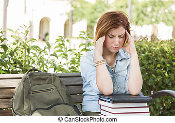 ung, kvinnligt studerande, med, huvudvärk, sittande, med, böcker, och, ryggsäck, på, campus, bench.