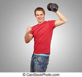 ung man, gör, fitness, med, vikter, över, grå, bakgrund