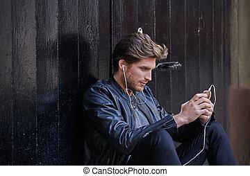 ung man, lyssnande, musik, smartphone, hörlurar
