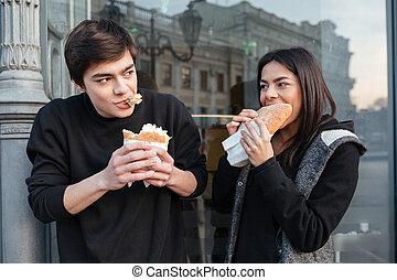 ung man, och, kvinna ätande, hamburgare, in, den, gata