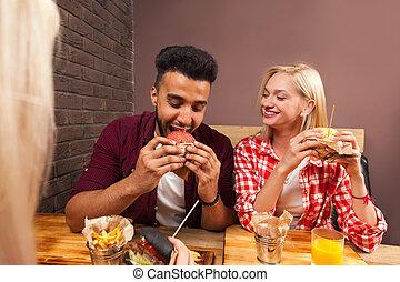 ung man, och, kvinna ätande, snabbmat, hamburgare, sittande, hos, trä tabell, in, cafe