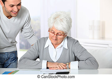 ung man, portion, äldre kvinna, med, skrivbordsarbete