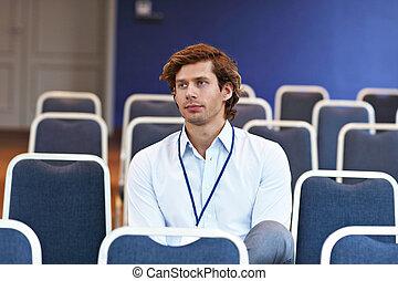 ung man, sittande, allena, in, möte rum