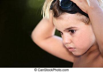 ung pojke, puttning på, simning skyddsglasögon