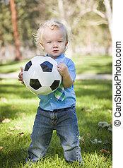 ung, söt, pojke, leka, med, fotboll bal, i park