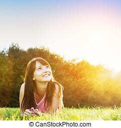 ung, vacker kvinna, le, och, lägga på gräset, hos, sommar, solnedgång