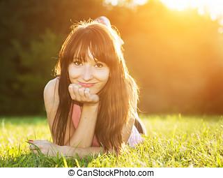 ung, vacker, naturlig, kvinna, lägga på gräset, hos, sommar, solnedgång