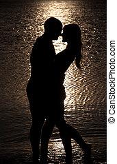 ungt par, klemme, silhuet, på, en, hav, strand, imod, solnedgang, baggrund