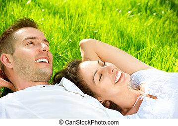 ungt par, lägga på gräs, utomhus