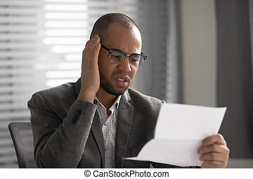 Unhappy African American businessman reading document, receiving bad news