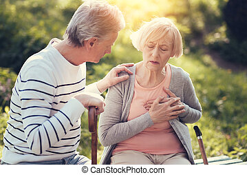 Unhappy aged woman holding her chest