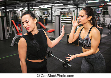 Unhappy and disgust young asian woman look back and keep eyes closed. She shows stop sign. European model try to call her and tell. They are in gym.