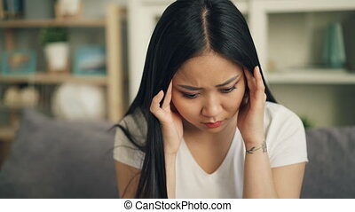 Unhappy Asian female student is feeling bad having headache...
