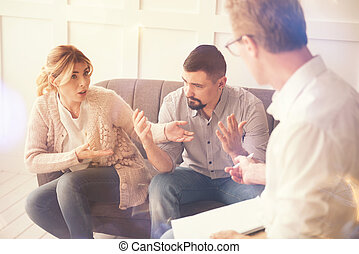 Unhappy blonde woman pointing at her husband