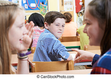 Unhappy Boy Being Gossiped About By School Friends In Classroom
