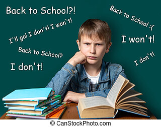 Unhappy boy of European appearance is sitting on the background of the school green board. Teen does not want to school. A stack of books and notebooks next to the student.
