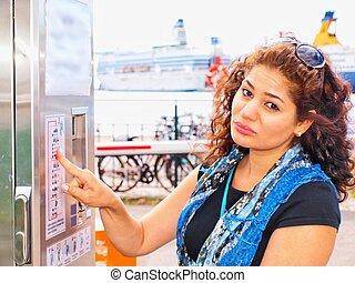 Unhappy brune, female, at ticket vending machine
