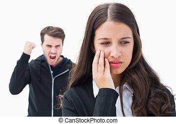 Unhappy brunette being threatened by boyfriend on white background