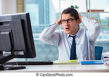 Unhappy businessman sitting at desk in office