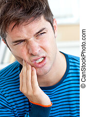 Unhappy caucasian man having a toothache in the living-room...