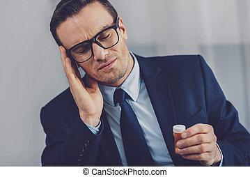 Unhappy cheerless man feeling headache