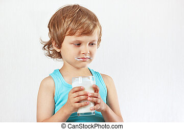 Unhappy child does not want to drink a fresh milk