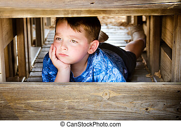 Unhappy child hiding and sulking while playing on playground...