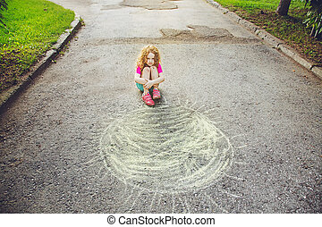 Unhappy child sitting in asfalt on a drawing sun.