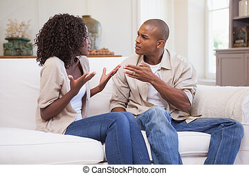 Unhappy couple arguing on the couch at home in the living...