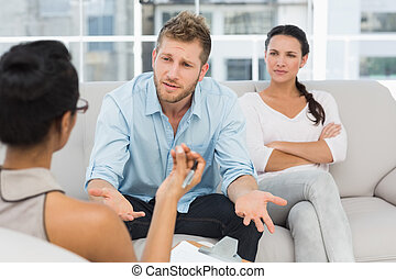Unhappy couple at therapy session with man talking to therapist
