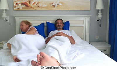 Unhappy couple fighting in bed room