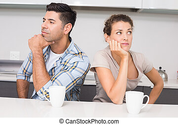 Unhappy couple having coffee not speaking at home in kitchen