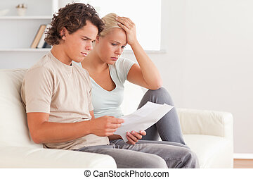 Unhappy couple holding an invoice in the living room