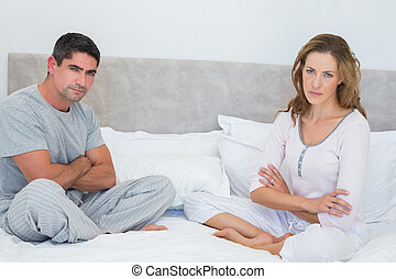Unhappy couple in bed - Portrait of unhappy couple sitting...