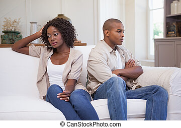 Unhappy couple not speaking to each other on sofa at home in...