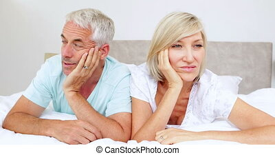 Unhappy couple not talking on bed