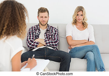 Unhappy couple not talking on the couch at therapy session