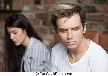 Unhappy couple sitting on couch at home