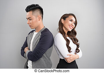 Unhappy couple standing back to back in a studio