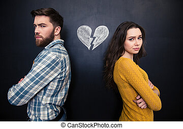 Unhappy couple standing over chalkboard background with...