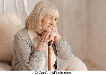 Unhappy depressed woman leaning on her walking stick
