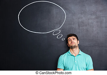 Unhappy despaired man over blackboard background with speech bubble