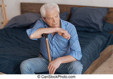 Unhappy elderly man sitting on the bed - Deep in thoughts....
