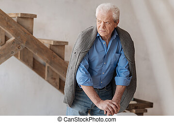 Unhappy elderly man standing in the room