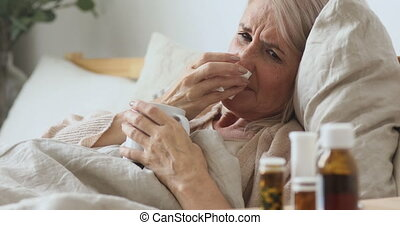 Head shot unhealthy middle aged older woman lying in bed under duvet with hot anti grippe beverage, suffering from runny nose. Unhappy elderly mature granny caught cold flu sneezing, taking medicine.