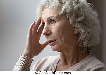 Unhappy elderly woman lost in thoughts in retirement house