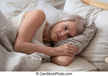 Unhappy elderly woman lying in bed thinking