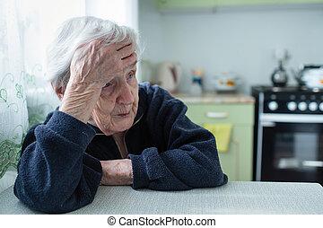 Unhappy elderly woman portrait near window in the house.