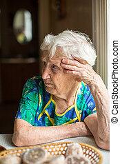 Unhappy elderly woman sitting