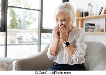 Unhappy elderly woman sneezing